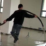 Ouvrier réalisant une chape liquide dans un bâtiment
